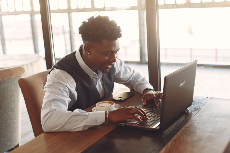 Canva - Positive young ethnic businessman working on laptop while sitting in cafe